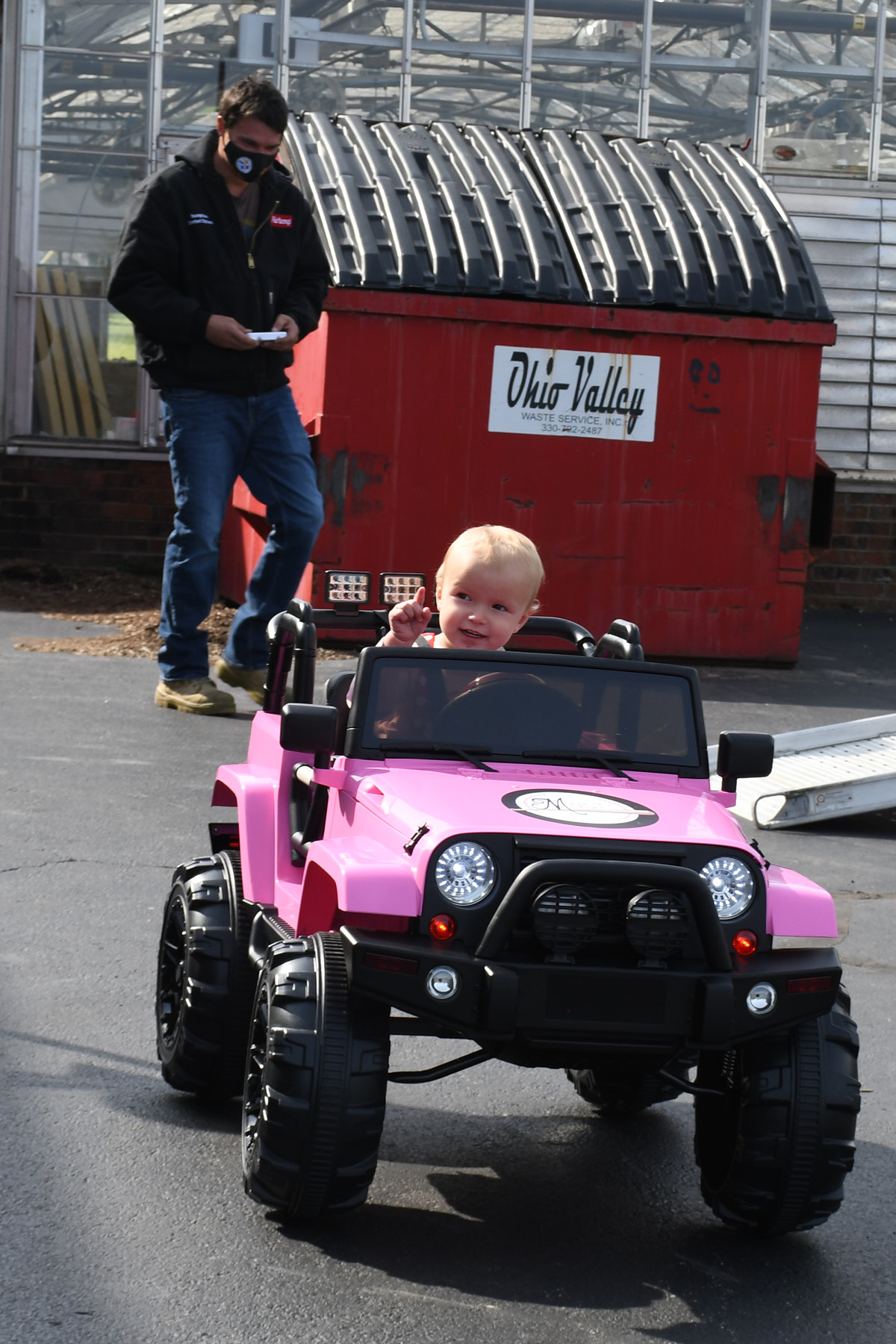 toddler in ride-on car, man in back with remote